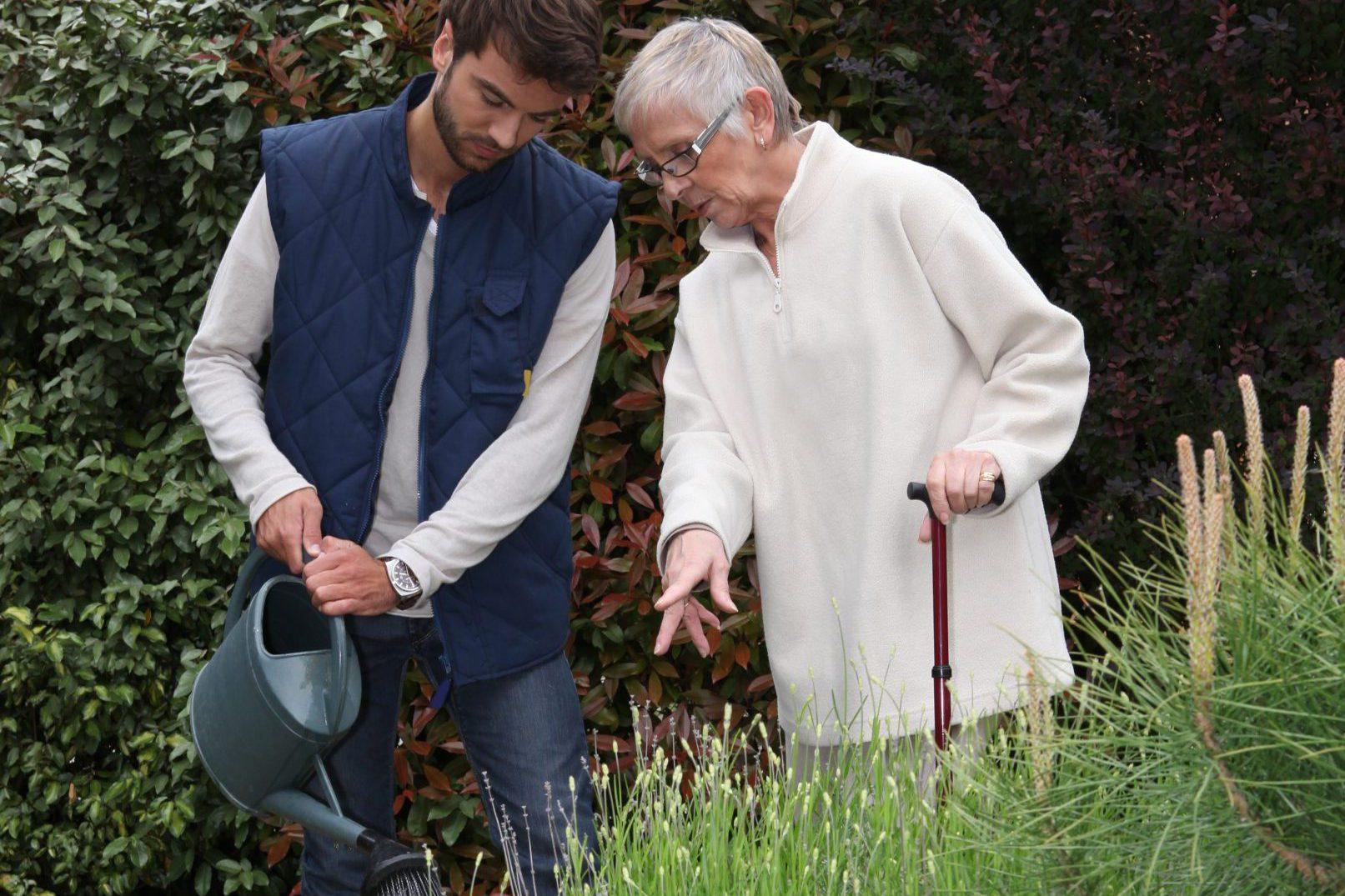 personne âgée avec une personne qui arrose les plantes